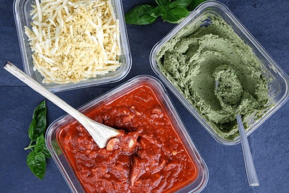 A display of mushroom tomato sauce, basil seed cheese, and parmesan-mozzarella blend