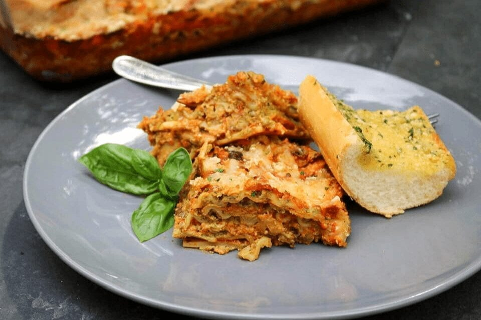 A plate with lasagna and garlic bread