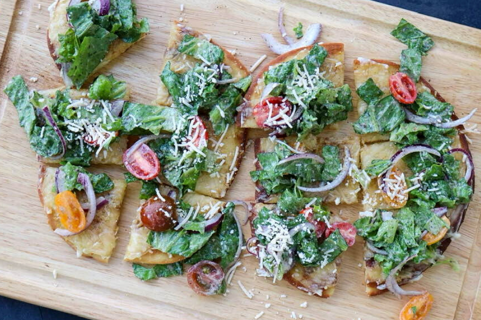 Looking down at two Caesar salad flatbreads