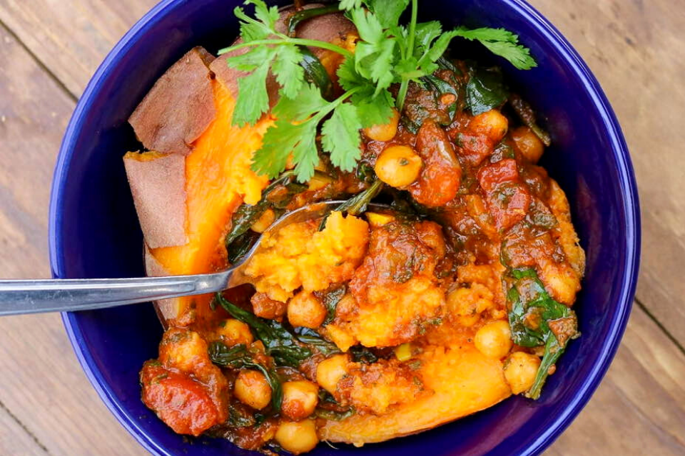 A bowl with a baked sweet potato and vegan Moroccan tagine on top