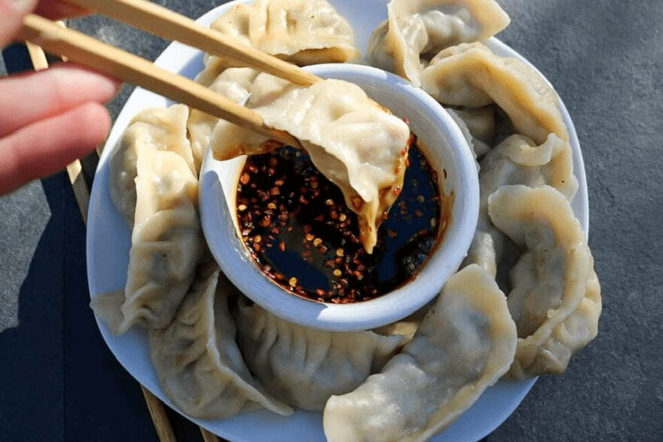 Dipping a potsticker into the sauce