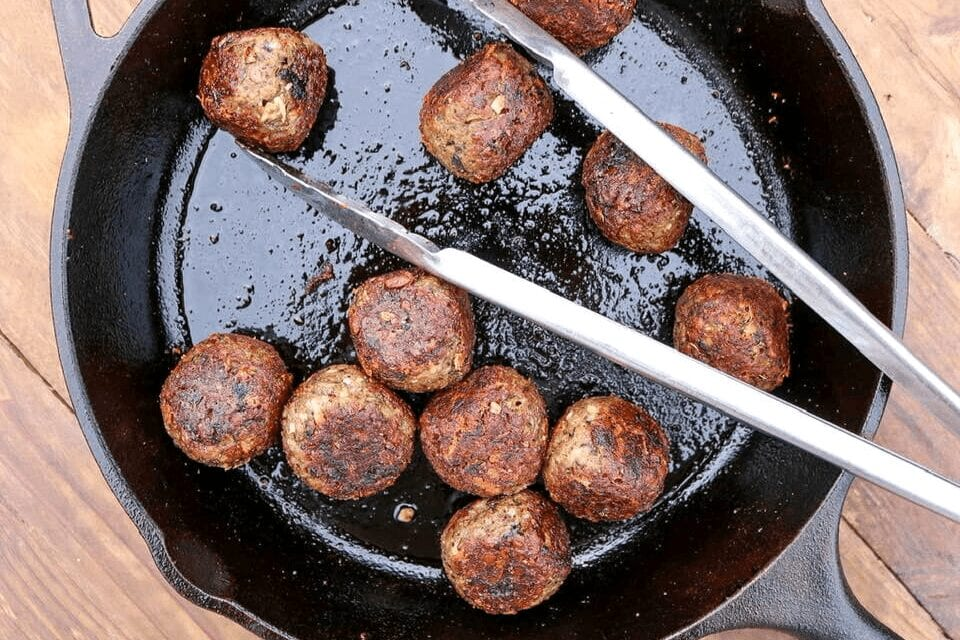 A cast-iron skillet with the vegan meatballs in it