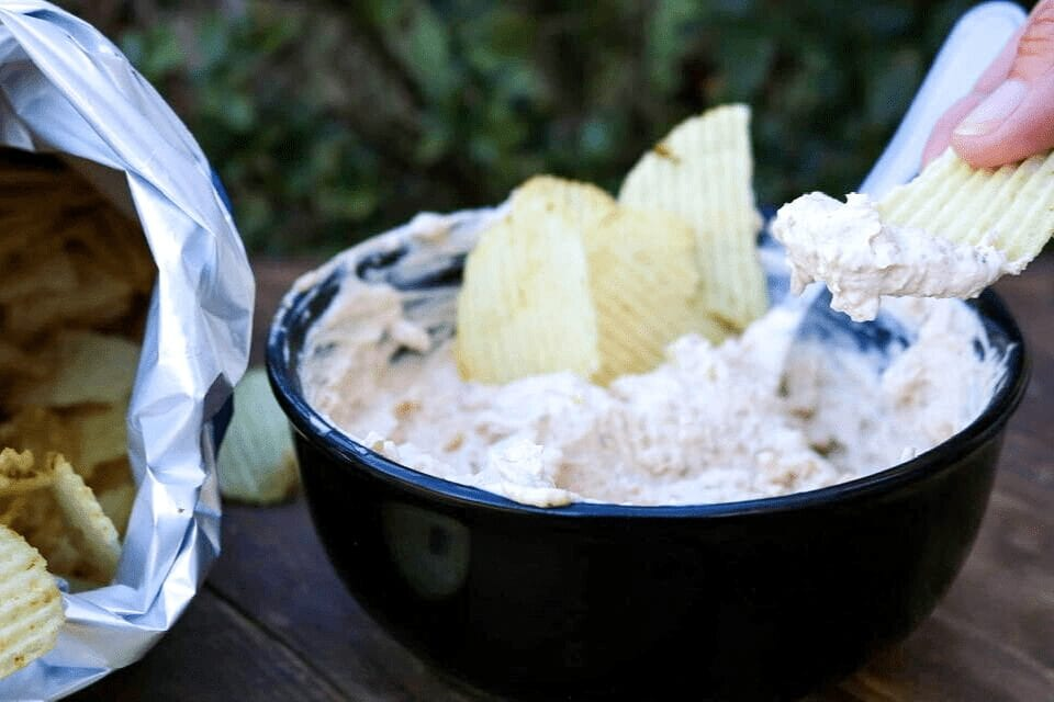 Dipping a potato chip into the vegan French onion dip