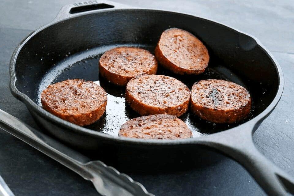A cast-iron skillet with vegan sausage patties