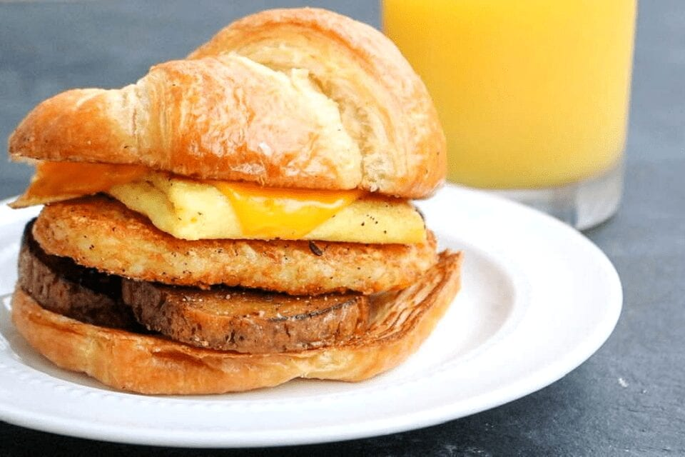 A vegan croissant breakfast sandwich with sausage patties, a hashrbrown, vegan egg patty and vegan cheese