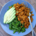 A plate with chickpea scramble, massaged kale, and avocado