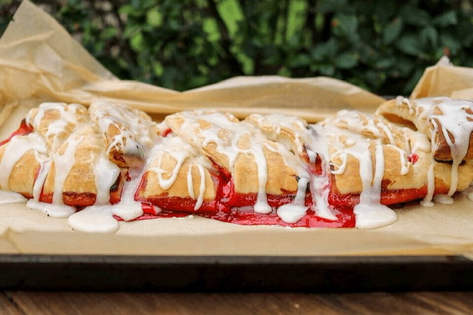 A look at the side of the strawberry and cream cheese danish with the icing dribbling over the edges