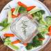 Vegan ranch dip served with raw broccoli, carrots, and celery