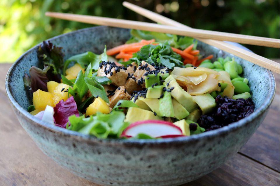 A salad bowl with greens, rice, tofu, veggies, mango, avocado, ginger, herbs, and a dressing!