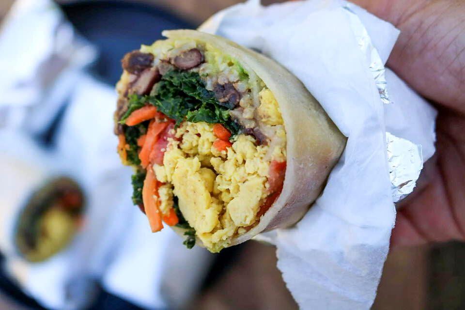 A vegan breakfast burrito filled with vegan scrambled eggs, rice, beans, and veggies!