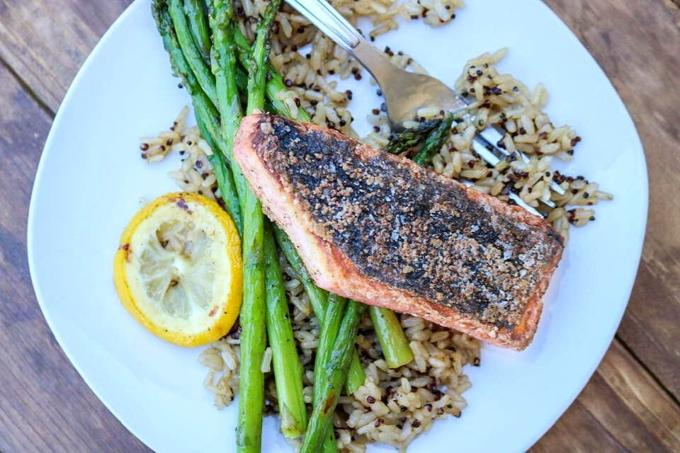 Vegan salmon fillet plated with mixed rice, asparagus, and a slice of lemon