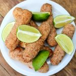 A plate full of vegan ham croquetas with lime wedges