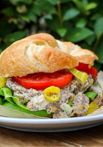 Vegan tuna salad in a croissant with lettuce, tomato, and banana peppers