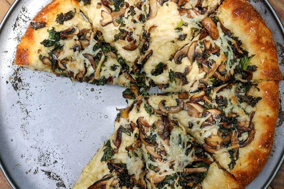 Stuffed crust vegan pizza with mushrooms and kale